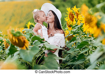 Happy mother in hat with the daughter in the field with sunflowers. mom and baby girl having fun outdoors. family concept. mom kisses her daughter