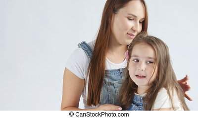 Happy Mother is brushing her lovely daughters hair on a...