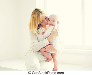 Happy mother kissing baby at home in white room near window