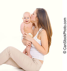 Happy mother kissing baby on a white background