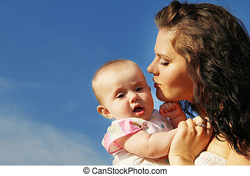Happy mother kissing baby over blue sky
