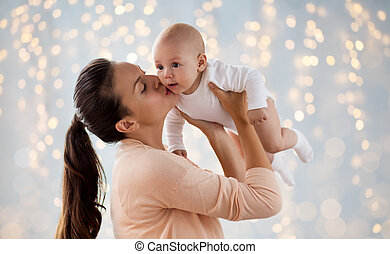 happy mother kissing little baby boy over lights