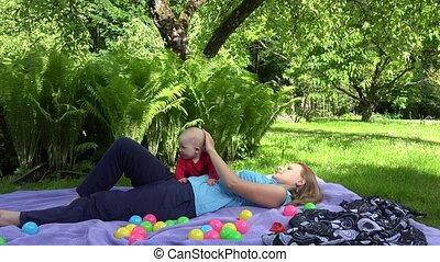 Happy mother lay on plaid with baby daughter on plaid in summer park. 4K