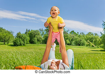 Happy mother lifting baby up with straight arms