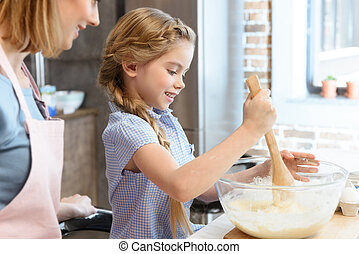 Happy mother looking at little daughter preparing dough in glass bowl