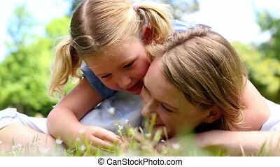 Happy mother lying on the grass with daughter - Happy mother...