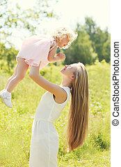 Happy mother playing having fun with child in summer day