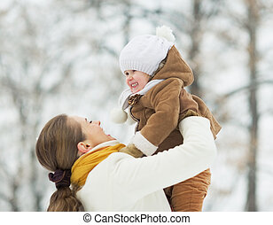 Happy mother playing with baby in winter outdoors