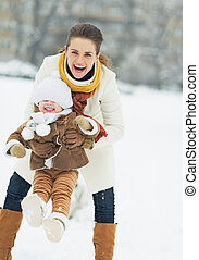 Happy mother playing with baby in winter park