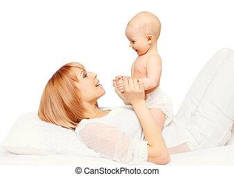 Happy mother playing with baby lying over white background