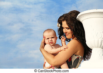 Happy mother playing with baby over blue sky