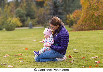 Happy mother playing with child in warm autumn day