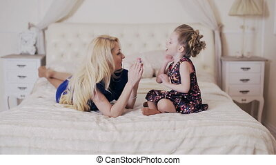 happy mother playing with daughter in the bedroom.