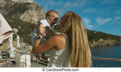 Happy mother playing with her little son outdoors