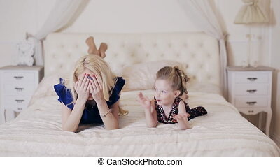 happy mother playing with kid in the bedroom.