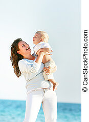 happy mother playing with son on sea background