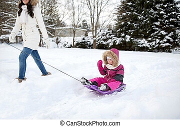 happy mother pulling sled with child in winter