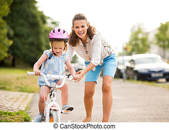 Happy mother pushes daughter on her bike as she learns to...