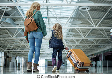 Happy mother putting his daughter on plane - Low angle of ...