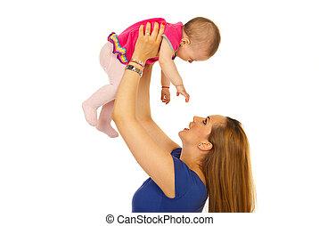 Happy mother raising  baby