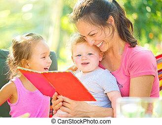 Happy mother reading a book to her children in sunny park