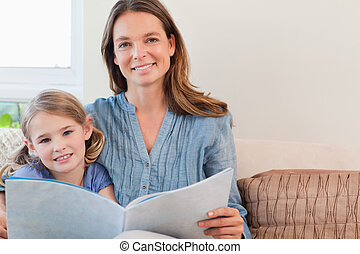 Happy mother reading a book to her daughter