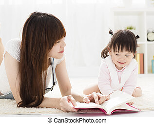 happy Mother reading book to daughter