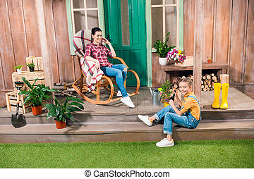 Happy mother sitting in rocking chair and smiling daughter cultivating plant on porch