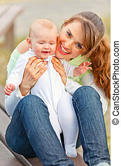 Happy mother sitting on bench in park and holding smiling...