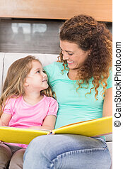 Happy mother sitting with her little daughter reading a storybook at home in living room