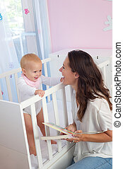 Happy mother smiling at baby in crib