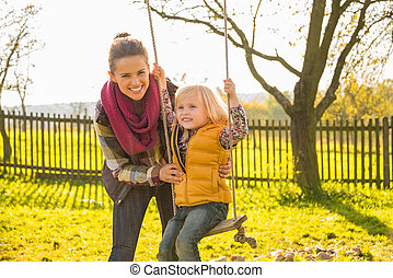 Happy mother swinging child outdoors