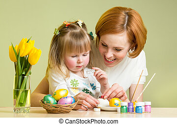 happy mother teaches kid daughter to decorate Easter eggs
