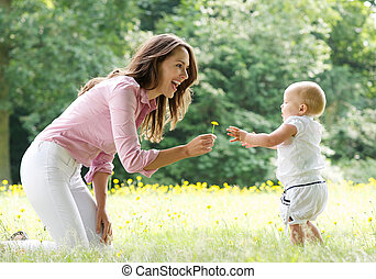 Happy mother teaching baby to walk in the park - Portrait of...