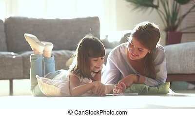 Happy mother teaching cute child girl drawing on warm floor