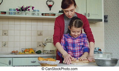 Happy mother teaching her little cute daughter rolling dough while cooking together in the kitchen at home on holidays. Family, food and people concept