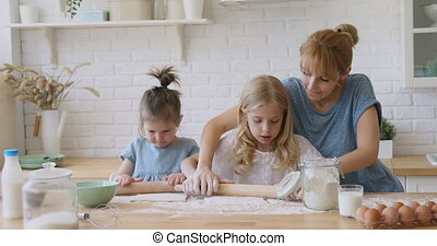 Happy mother teaching kids daughters rolling dough in kitchen