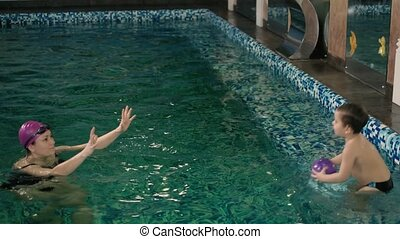 Happy mother teaching to son in swimming pool 4k
