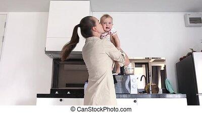 Happy mother throws baby white kitchen background - Happy...