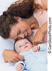 Happy mother tickling baby boy in bed