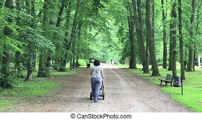 Happy mother walking with baby stroller