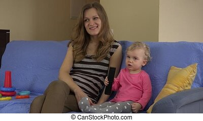 happy mother watch TV with baby daughter sit on sofa indoor. 4K