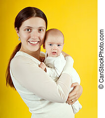 Happy mother with 2 month baby over yellow background