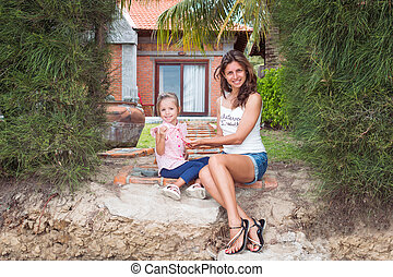 Happy mother with a child sitting on the grass