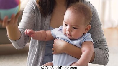 happy mother with baby and ball playing at home - family and...