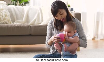 happy mother with baby and ball playing at home