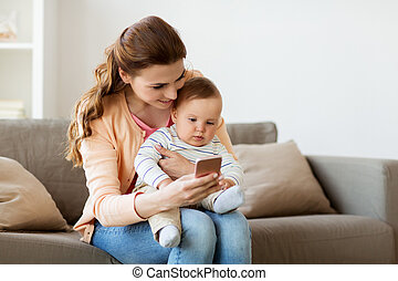 happy mother with baby and smartphone at home