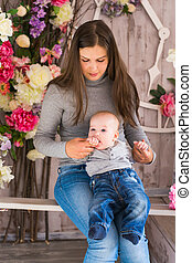 Happy mother with baby boy in the room