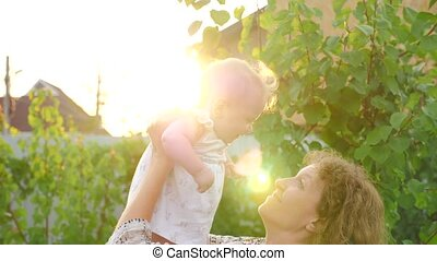 Happy mother with baby girl. Baby with smiling face is waving on mother's hands. Lens reflection.
