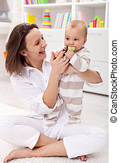 Happy mother with baby girl playing